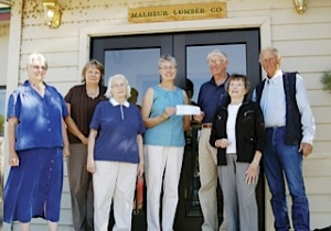 John Shelk presenting a check to Tracie Unterwegner and members of the Grant County Library Foundation to purchase land for new library.